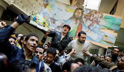 """With our blood and soul, we redeem the cross,"" Coptic Christians chant after Mass on Sunday, Jan. 2, 2011, at Saints Church in Alexandria, Egypt, where 21 were killed by a suicide bomber. They carried a blood-spattered poster depicting Jesus. (AP Photo)"