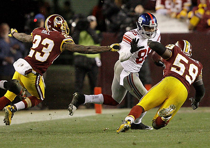 Washington Redskins cornerback DeAngelo Hall (23) and Redskins linebacker London Fletcher (59) pursue New York Giants wide receiver Derek Hagan (85) during the second half of an NFL football game in Landover, Md., on Sunday, Jan. 2, 2011. The Giants won, 17-14. (AP Photo/Jacquelyn Martin)