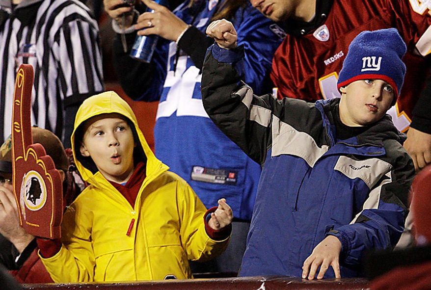 Washington Redskins and New York Giants fans dance during the second half of an NFL football game in Landover, Md., on Sunday, Jan. 2, 2011. The Giants won, 17-14. (AP Photo/Jacquelyn Martin)