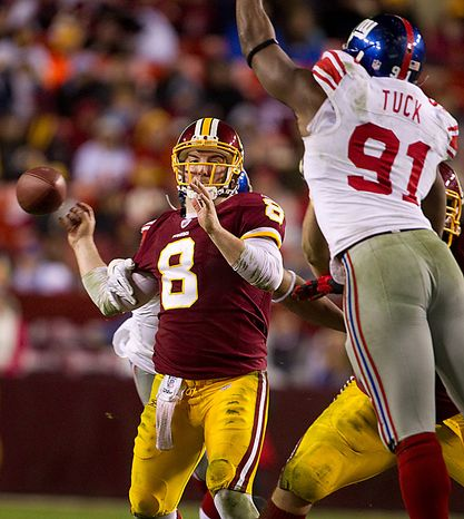 Washington Redskins quarterback Rex Grossman (8) fumbles the ball as he is hit by New York Giants defensive end Osi Umenyiora (72) during the second half of an NFL football game on Sunday, Jan. 2, 2011, in Landover, Md. The Giants defeated the Redskins, 17-14, but were eliminated from the playoffs with a Green Bay Packers victory over the Chicago Bears. At right is New York Giants defensive end Justin Tuck (91). (AP Photo/Evan Vucci)
