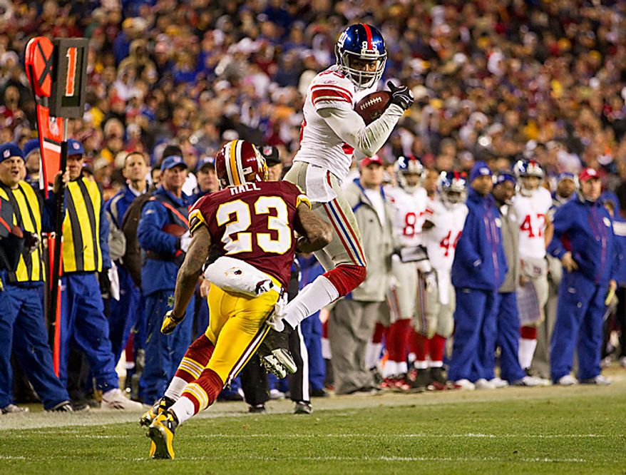 New York Giants wide receiver Derek Hagan (right) makes a catch over Washington Redskins cornerback DeAngelo Hall (23) during the second half of an NFL football game on Sunday, Jan. 2, 2011, in Landover, Md.  The Giants defeated the Redskins, 17-14, but were eliminated from the playoffs with a Green Bay Packers victory over the Chicago Bears.  (AP Photo/Evan Vucci)