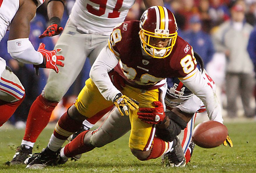 Washington Redskins wide receiver Santana Moss (89) drops the ball as he is tackled by New York Giants linebacker Jonathan Goff (54) during the second half of an NFL football game in Landover, Md., on Sunday, Jan. 2, 2011. The Giants won 17-14. (AP Photo/Jacquelyn Martin)