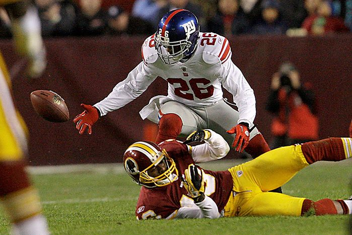New York Giants safety Antrel Rolle (26) scrambles for the ball after knocking it from Washington Redskins wide receiver Anthony Armstrong (13) during the first half of an NFL football game in Landover, Md., on Sunday, Jan. 2, 2011. (AP Photo/Jacquelyn Martin)