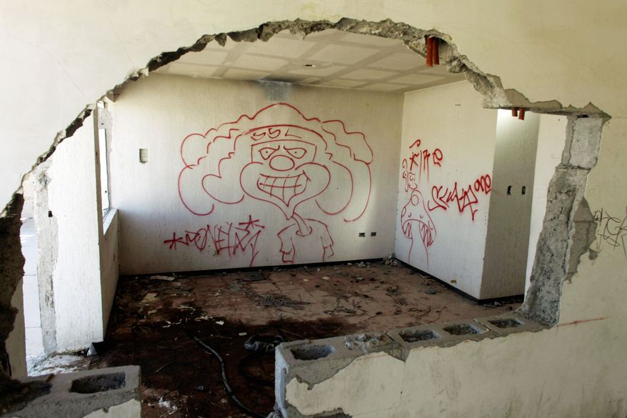 Graffiti covers the shell of a home in a nearly abandoned working-class neighborhood. No one knows how many have fled the city. (Associated Press)