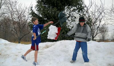 "Jack Rogers, 12, and his brother Maxwell, 9, enjoy the snowfall in Fishers, Ind., last week. Jack said he knows ""lots of kids"" who dress light in winter. ""Coats are just a hassle, putting it all on. It makes me bulky."" he says. (Shelley Rogers Landes via Associated Press)"