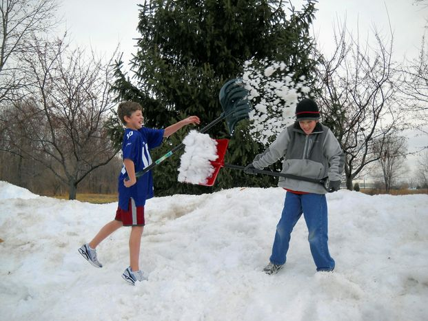 """Jack Rogers, 12, and his brother Maxwell, 9, enjoy the snowfall in Fishers, Ind., last week. Jack said he knows """"lots of kids"""" who dress light in winter. """"Coats are just a hassle, putting it all on. It makes me bulky."""" he says. (Shelley Rogers Landes via Associated Press)"""