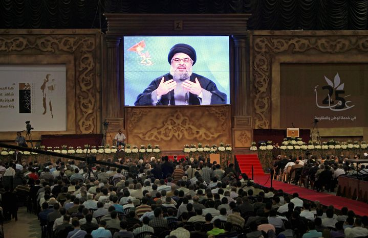 Hezbollah leader Sheik Hassan Nasrallah is seen on a big screen as he speaks in a Beirut suburb in November. He says the threat of indictments against Hezbollah for the assassination of former Prime Minister Rafik Hariri are not a concern, but analysts say otherwise. Mr. Nasrallah has called for other Lebanese to back his group. (Associated Press)
