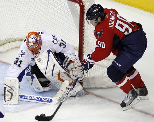 Washington Capitals' Marcus Johansson (90), of Sweden, attempts a shot on Tampa Bay Lightning goalie Dwayne Roloson (31) during the second period of an NHL hockey game, Tuesday, Jan. 4, 2011, in Washington. The Lightning won 1-0 in overtime. (AP Photo/Luis M. Alvarez)