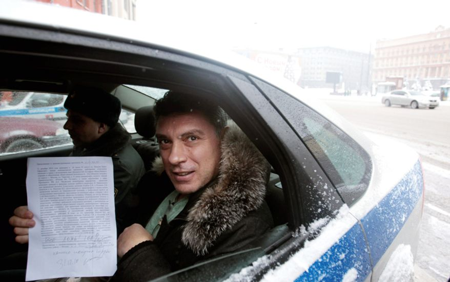 UNDER ARREST: Russian opposition leader Boris Nemtsov displays a protocol paper as he is escorted to court in Moscow. (Associated Press)