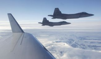 A pair of U.S.-built NORAD F-22 fighter jets fly off the wing of a civilian airplane playing the role of a hijacked airliner over a mountainous area of Alaska on Aug. 10, 2010, at the end of a route from an undisclosed location in the Far East to Alaska. The first-of-its-kind hijacking exercise involving the U.S., Canadian and Russian militaries went so well that a similar drill is planned for 2011. (AP Photo/Ted S. Warren, File) ** FILE **