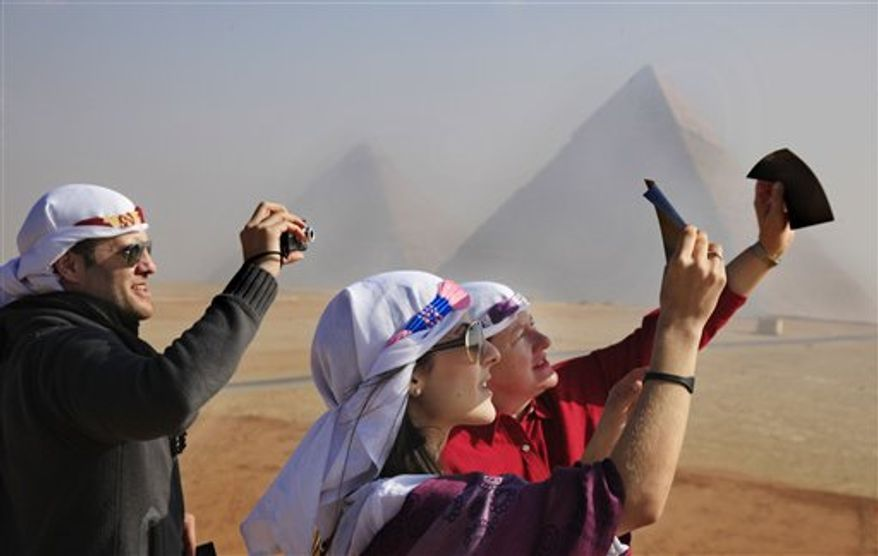 Venezuelan tourists watch a partial solar eclipse in front of the Giza Pyramids, Egypt, Tuesday, Jan. 4, 2011. A partial solar eclipse began Tuesday in the skies over the Mideast and extended across much of Europe. (AP Photo/Amr Nabil)
