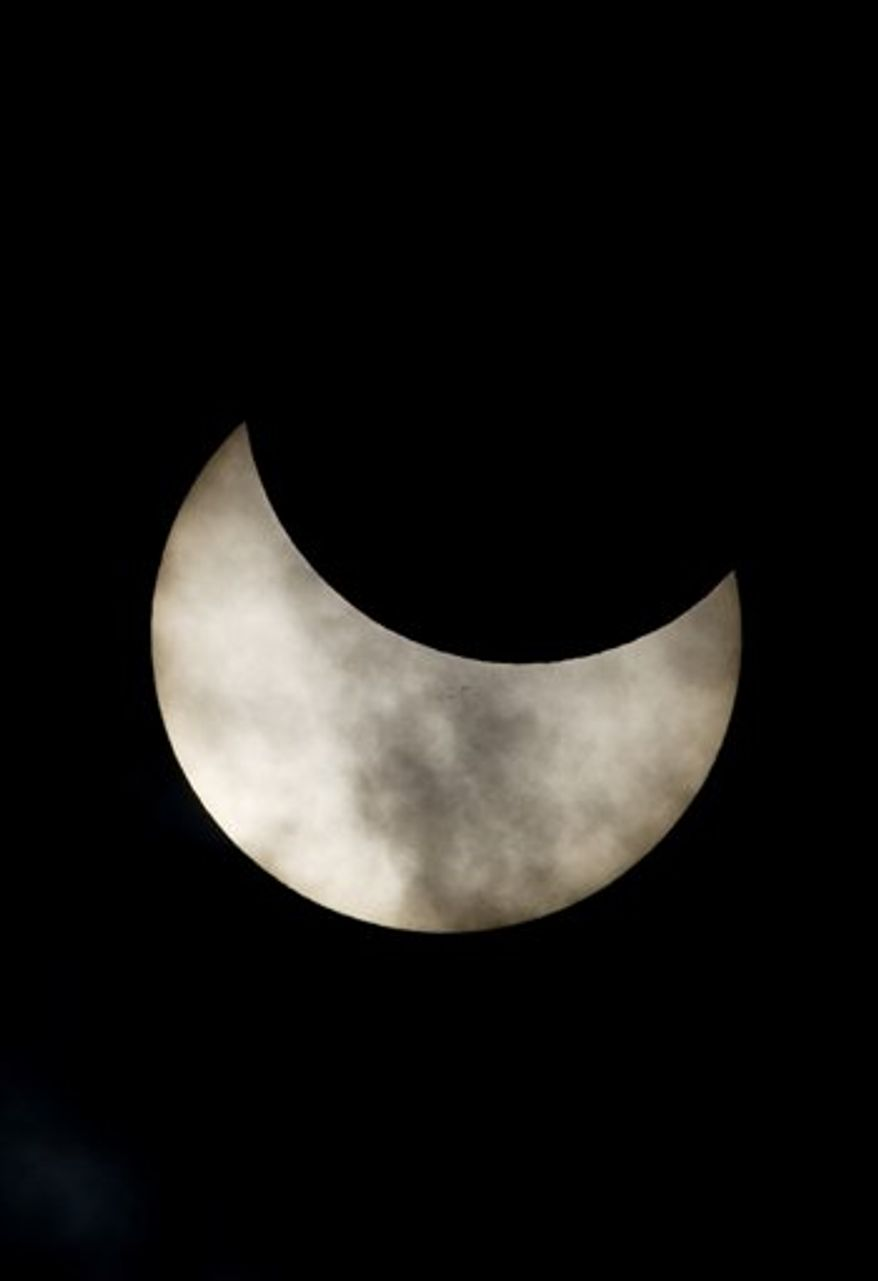 A view of a partial solar eclipse as seen from the town of Givatayim near Tel Aviv, Israel, Tuesday, Jan. 4, 2011. A partial solar eclipse began Tuesday in the skies over the Mideast and extended across much of Europe. (AP Photo/Ariel Schalit)