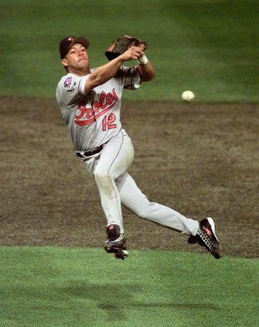 FILE - In this Oct. 12, 1997, file photo, Baltimore Orioles' Roberto Alomar throws out Cleveland Indians' Bip Roberts to end the fourth inning of Game 4 of the American League Championship Series at Jacobs Field in Cleveland, Ohio. Alomar and Bert Blyleven hope they're on dec