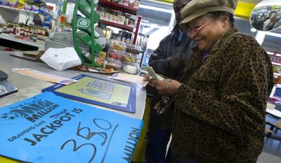 Loretta Pride (right) smiles after receiving help from Ivey Coples with selecting numbers for three Mega Millions lottery tickets at the All in One Shop in Greensboro, N.C., on Tuesday, Jan. 4, 2011. (AP Photo/News & Record, Jerry Wolford)