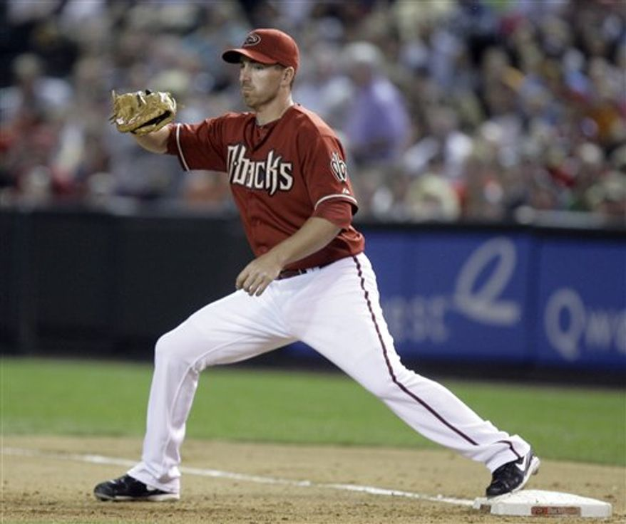 In this April 7, 2010, photo, Arizona Diamondbacks first baseman Adam LaRoche catches a throw during a baseball game against the San Diego Padres in Phoenix. A person familiar with the negotiations tells The Associated Press that the Washington Nationals and free-agent first baseman LaRoche have agreed to a two-year contract, pending a physical. (AP Photo/Paul Connors)