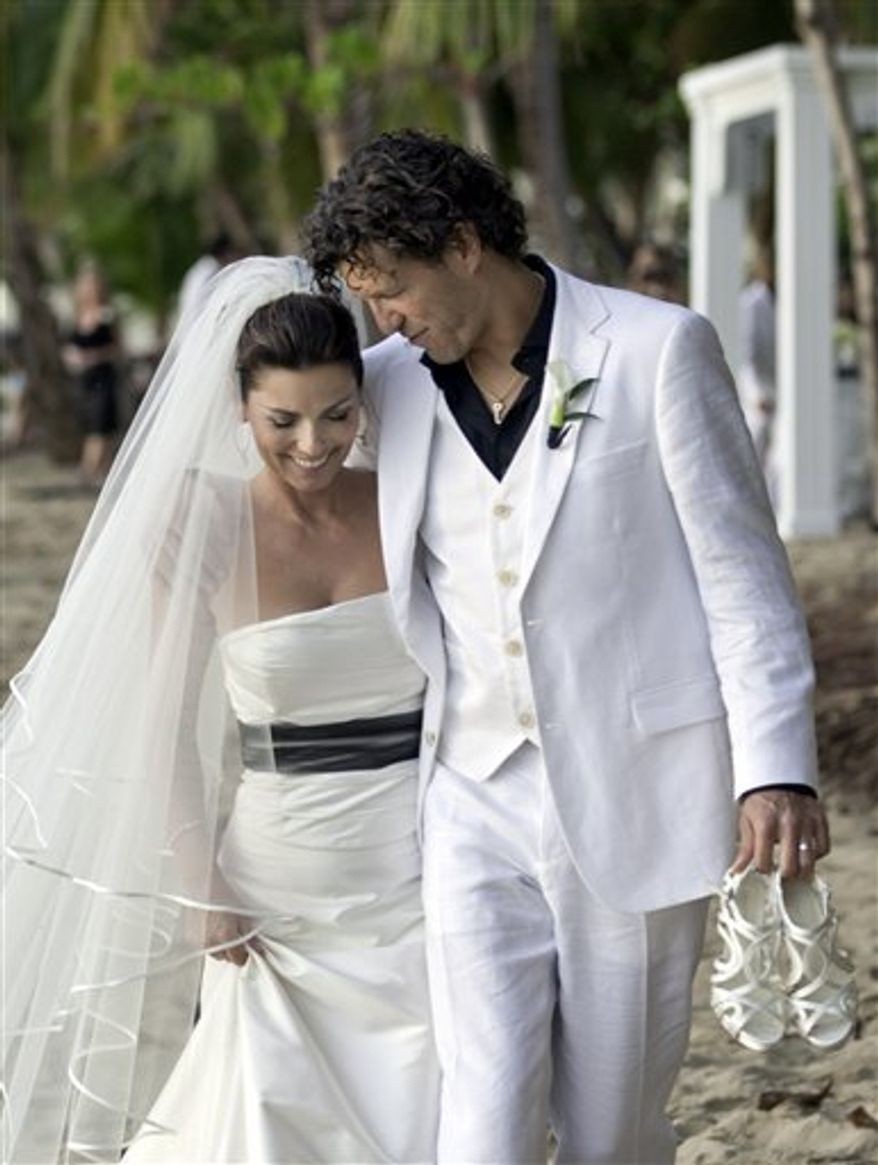 In this Jan. 1, 2011 publicity image released by Sandbox Entertainment, country singer Shania Twain, left, and her husband Frederic Thiebaud are shown on their wedding day in Rincon, Puerto Rico.  (AP Photo/Sandbox Entertainment) NO SALES, FOR EDITORIAL USE ONLY