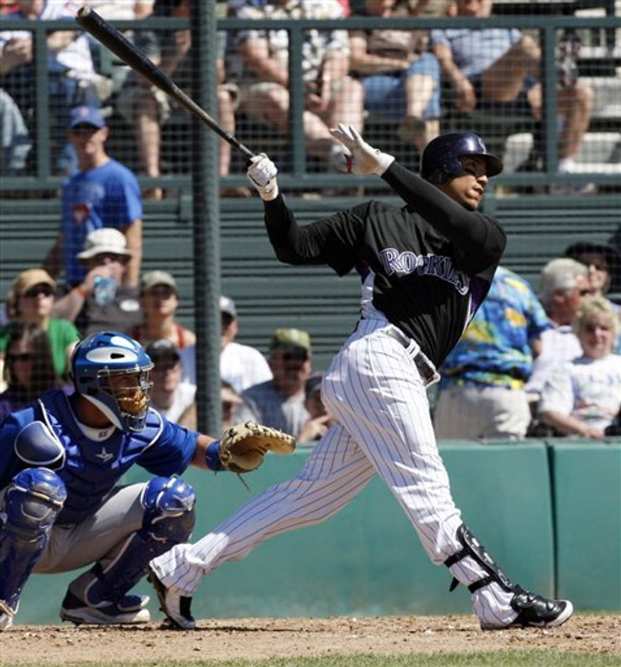 """FILE-In this  March 15, 2010 file photo, Colorado Rockies Carlos Gonzalez follows through after hitting for a double in a Cactus League spring training baseball game against the Chicago Cubs in Tucson, Ariz. The publicist for Gonzalez  said Monday Jan. 3, 2011, an $80 million, seven-year contract for the Colorado Rockies outfielder is """"practically finalized."""" (AP Photo/Ed Andrieski,File)"""