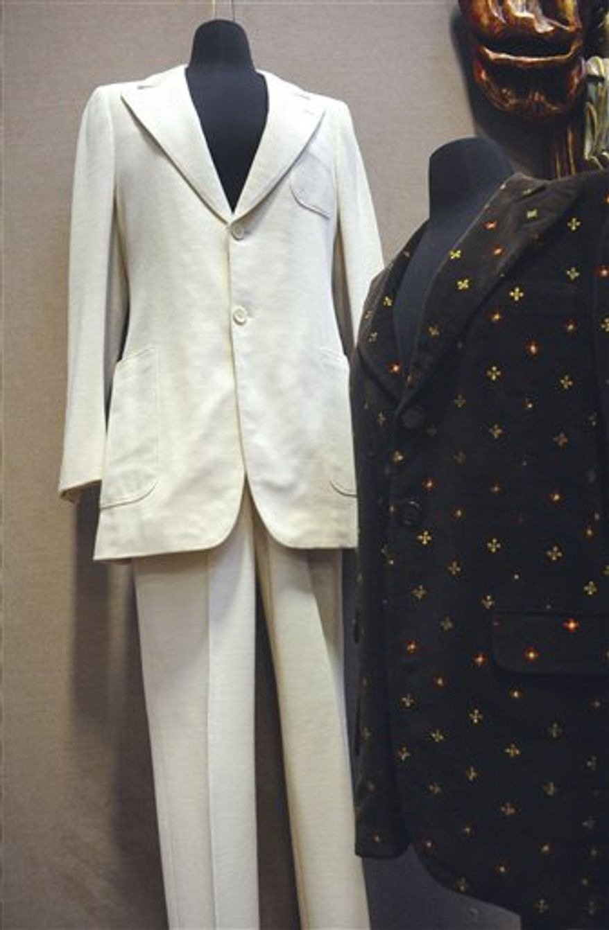"""FILE -- This Monday, Dec. 13, 2010 file photo shows two outfits worn by John Lennon at the Braswell Galleries in Norwalk, Conn. On the left is the suit Lennon wore in the photo on the cover of the The Beatles' Abbey Road album. On the right is a blazer he wore during his video for the song """"Imagine."""" The white, two-piece suit sold at auction for $46,000 Saturday Jan. 2011.  (AP Photo/The Hour, Matthew Vinci/file) MANDATORY CREDIT"""