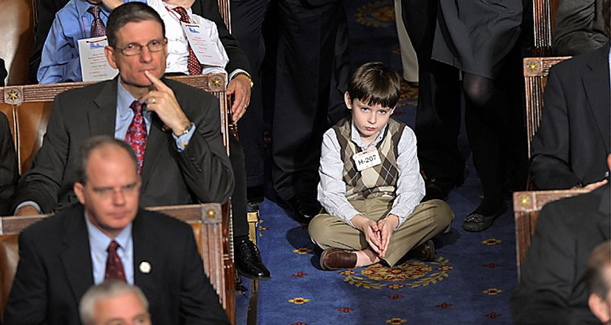 A family member of a House member sits on the floor during the first session of the 112th Congress on Capitol Hill in Washington, Wednesday, Jan. 5, 2011.  (AP Photo/Susan Walsh)