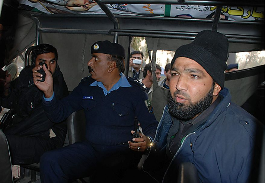 Mumtaz Qadri, right, the bodyguard who allegedly killed Punjab Gov. Salman Taseer, sits in police custody in Islamabad, Pakistan, on Tuesday, Jan. 4, 2011. An intelligence official interrogating the suspect told the Associated Press that the bearded elite force police commando was boasting about the assassination, saying he was proud to have killed a blasphemer. The killing was the highest-profile assassination of a political figure in Pakistan since the slaying of former Prime Minister Benazir Bhutto in December 2007. (AP Photo/Irfan Ali)