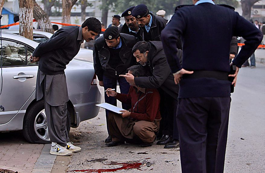 Pakistani police officers collect evidence at the scene where Punjab Gov. Salman Taseer was shot dead allegedly by one of his guards in Islamabad, Pakistan, on Tuesday, Jan. 4, 2011. (AP Photo/Muhammed Muheisen)