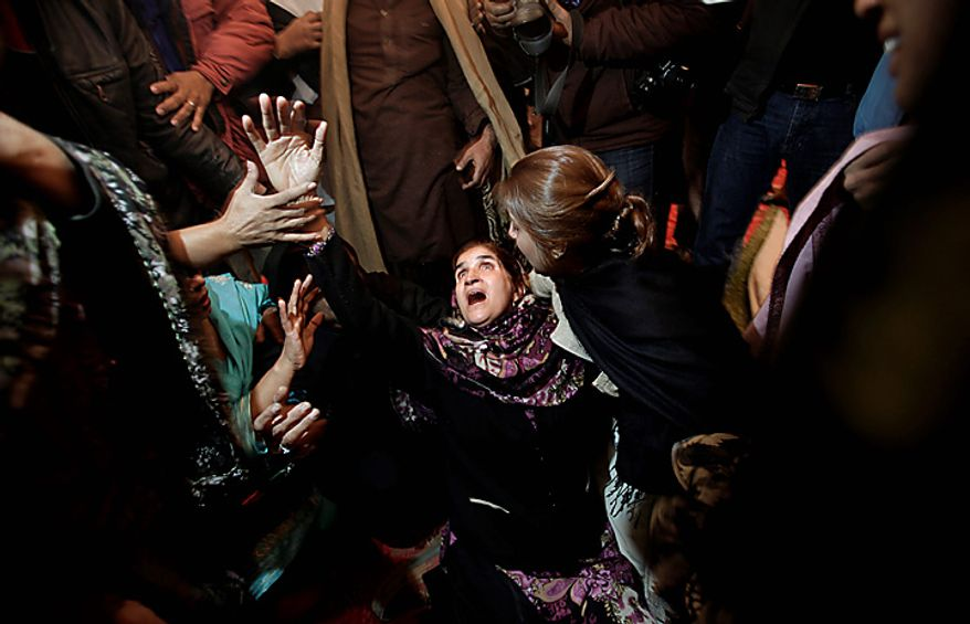 A Pakistani mourner grieves during the funeral procession of Punjab Gov. Salman Taseer in Lahore, Pakistan, on Wednesday, Jan. 5, 2011. Thousands of Pakistani police were on high alert in Lahore ahead of the funeral for the outspoken provincial governor, who was shot dead allegedly by a bodyguard reportedly enraged by Mr. Taseer's opposition to laws decreeing death for insulting Islam. Mr. Taseer, a high-profile, 66-year-old businessman and media tycoon, was a stalwart of the ruling Pakistan People's Party, and his assassination Tuesday sent nuclear-armed Pakistan reeling at a time of great political turmoil. (AP Photo/Muhammed Muheisen)