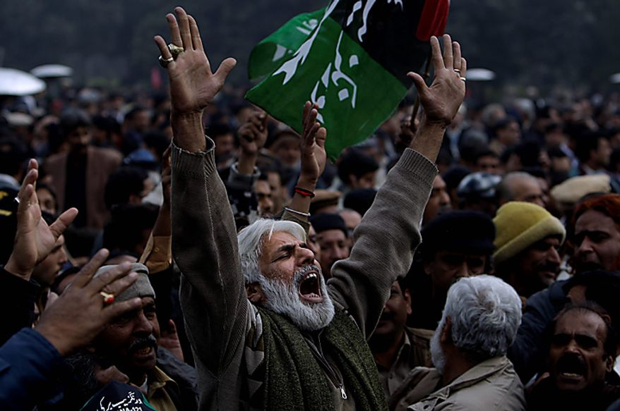 A Pakistani mourner reacts during the funeral procession of Punjab Gov. Salman Taseer in Lahore, Pakistan, on Wednesday, Jan. 5, 2011. Thousands of Pakistani police were on high alert in Lahore ahead of the funeral for the outspoken provincial governor, who was shot dead allegedly by a bodyguard reportedly enraged by Mr. Taseer's opposition to laws decreeing death for insulting Islam. Mr. Taseer, a high-profile, 66-year-old businessman and media tycoon, was a stalwart of the ruling Pakistan People's Party, and his assassination Tuesday sent nuclear-armed Pakistan reeling at a time of great political turmoil. (AP Photo/Muhammed Muheisen)