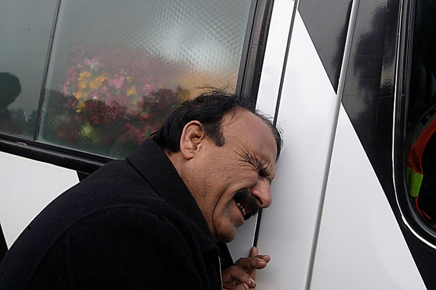 A Pakistani mourner grieves on an ambulance carrying the coffin of Punjab Gov. Salman Taseer during his funeral procession in Lahore, Pakistan, on Wednesday, Jan. 5, 2011. Thousands of Pakistani police were on high alert in Lahore on ahead of the funeral for the outspoken provincial governor, allegedly shot dead by a bodyguard reportedly enraged by his opposition to laws decreeing death for insulting Islam. Mr. Taseer, a high-profile, 66-year-old businessman and media tycoon, was a stalwart of the ruling Pakistan People's Party, and his assassination sent nuclear-armed Pakistan reeling at a time of great political turmoil. (AP Photo/K.M. Chaudary)