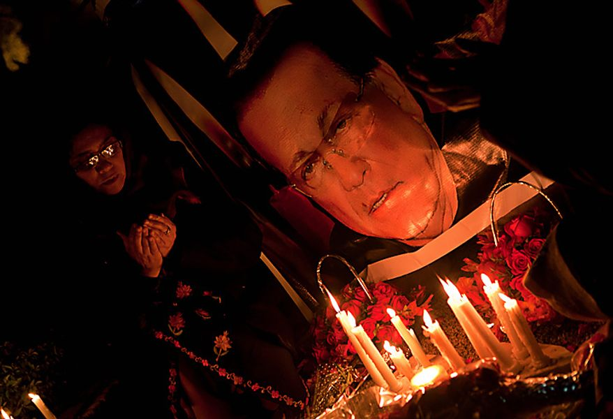 Pakistani women light candles and pray at the site of a shooting that killed Salman Taseer, governor of Pakistan's Punjab province, in Islamabad, Pakistan, on Wednesday, Jan. 5, 2011. Mr. Taseer was killed on Tuesday by his bodyguard commando, who reportedly was enraged by Mr. Taseer's opposition to laws decreeing death for insulting Islam. (AP Photo/B.K. Bangash)