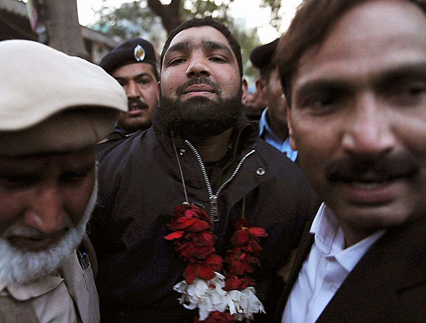 Mumtaz Qadri, center, the accused killer of Punjab Gov. Salman Taseer, arrives at court in Islamabad, Pakistan, on Wednesday, Jan. 5, 2011. More than 500 Muslim scholars  praised the man suspected of killing the Pakistani governor because the politician opposed blasphemy laws that mandate death for those convicted of insulting Islam. The group of scholars and clerics known as Jamat Ahle Sunnat is affiliated with a moderate school of Islam and represents the mainstream Barelvi sect. The group said in a statement Wednesday that no one should pray for Mr. Taseer or express regret for his murder. (AP Photo/B.K.Bangash)