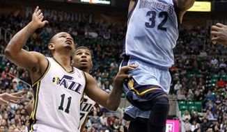Memphis Grizzlies guard O.J. Mayo (32) shoots the ball as he sails by Utah Jazz guard Earl Watson (11) during the first half of their NBA basketball game in Salt Lake City, Saturday, Jan. 1, 2011. (AP Photo/Steve C. Wilson)