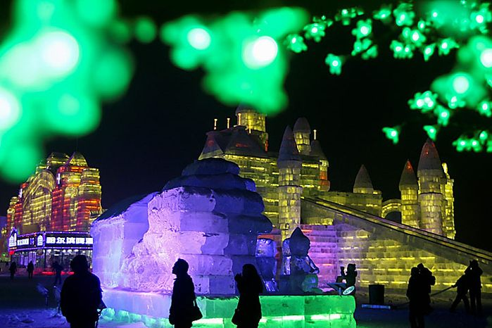 Visitors walk near ice sculptures at the annual Harbin Ice and Snow Festival in Harbin, in northeast China's Heilongjiang province, on