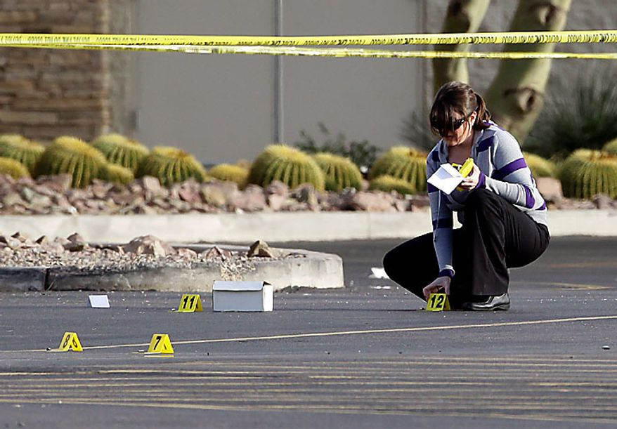 A law enforcement official marks bullet casings in the parking lot Wednesday, Jan. 5, 2011 outside the Chandler Mall in Chandler, Ariz. following a shooting at the Mall. (AP Photo/Matt York)