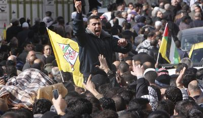 Palestinian mourners shout slogans as they carry the body, covered left, of Palestinian Omar Kawasmeh during his funeral in the West Bank city of Hebron, Friday, Jan. 7, 2011. Israeli troops mistakenly shot and killed the 65-year-old Palestinian man Friday during a predawn raid to arrest a Hamas militant in the West Bank, Palestinian officials said. (AP Photo/Nasser Shiyoukhi)