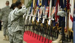 ** FILE ** In this Wednesday, Dec. 8, 2010 photo, soldiers pay their final respects to 13 fallen soldiers during the monthly Eagle Remembrance Ceremony at the Family Resource Center at Fort Campbell, Ky. (AP Photo/The Leaf-Chronicle, Jake Lowary)