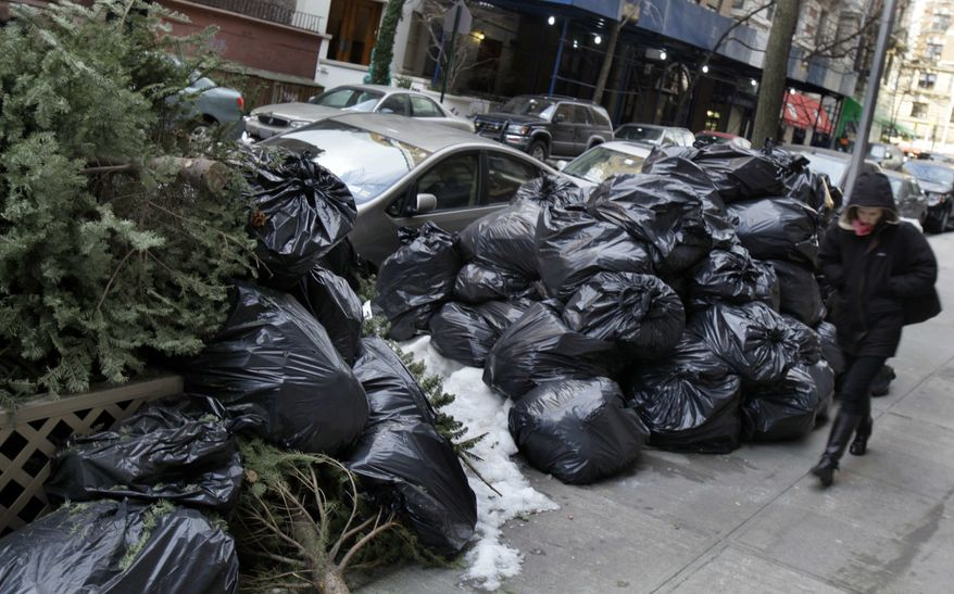 A woman walks by bags of uncollected trash and discarded Christmas trees on New York's Upper West Side on Thursday, Jan. 6, 2011. (AP Photo/Richard Drew) ** FILE **