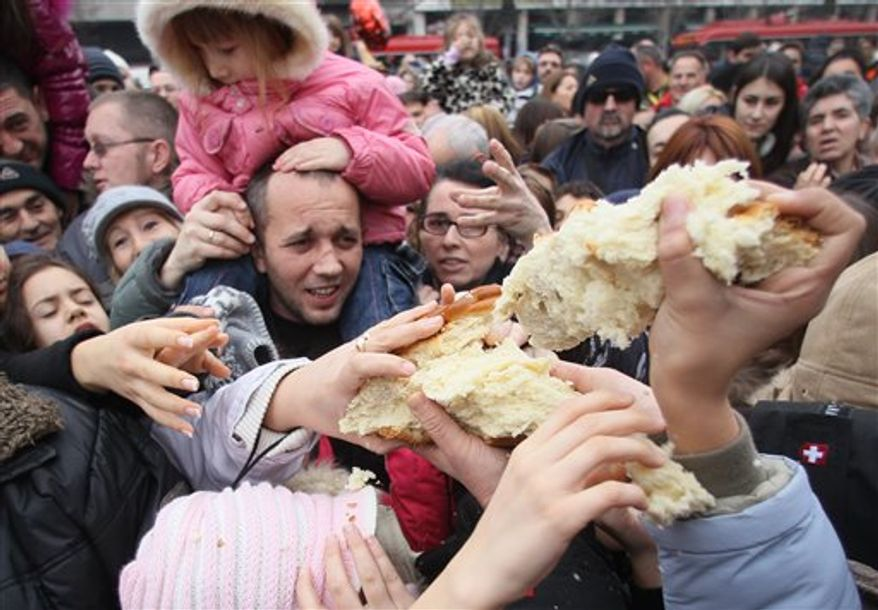 Christian Serb Orthodox believers break traditional Christmas bread to mark the Orthodox Christmas Day festivities in Belgrade, Serbia, on Friday, Jan. 7, 2011. Children traditionally scramble for a piece of the bread, searching for a gold coin, hidden inside. Orthodox Christians in Serbia celebrate Christmas on Jan. 7, according to the Julian calendar. (AP Photo/Darko Vojinovic)