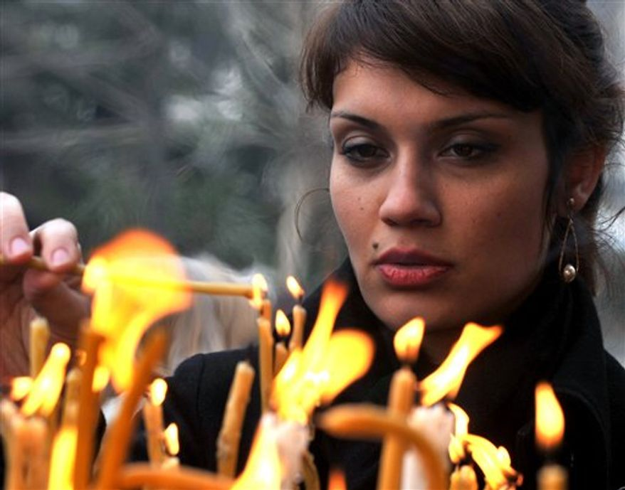 A woman lights candles during a holy Christmas liturgy in St. Clement's Cathedral in Macedonia's capital Skopje on Friday, Jan. 7, 2011. Macedonian Christian Orthodox believers celebrate Christmas by the Julian calendar. (AP Photo/Boris Grdanoski)