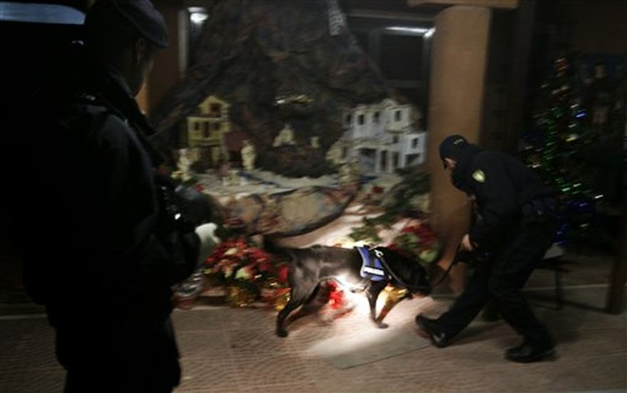 Italian police officers with a sniffing dog inspect a Nativity scene outside a Coptic Orthodox church during the Christmas Mass in Rome on Thursday, Jan. 6, 2011. Christian Copts in Europe are under police protection following Internet threats against their European places of worship, even as some prepare special services in honor of the 21 Copts killed in a weekend massacre at a church in their Egyptian homeland. (AP Photo/Riccardo De Luca)