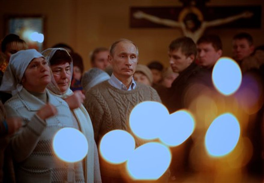 ** FILE ** Russian Prime Minister Vladimir Putin, foreground, crosses himself as he attends an Orthodox Christmas service in the XIX century church of the Protecting Veil of the Mother of God in Turginovo village, about 160 kilometers (100 miles) northwest of Moscow, Russia, on Friday, Jan. 7, 2011. (AP Photo/Alexander Zemlianichenko, Pool)