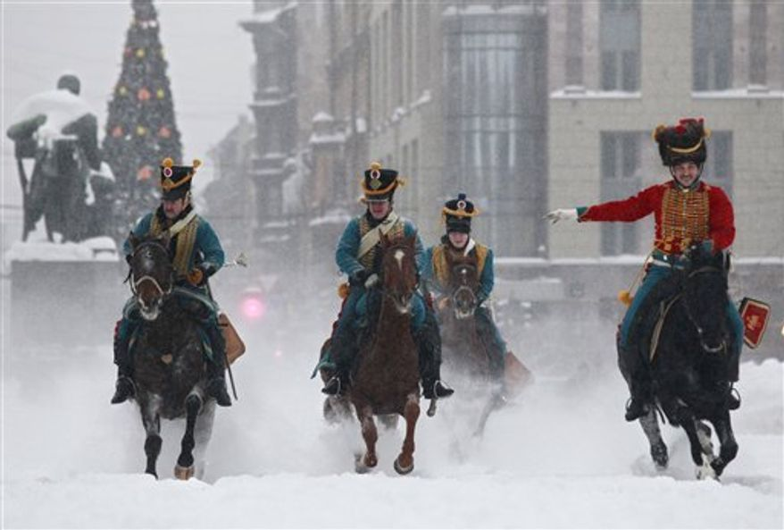 Riders dressed as soldiers of the Russian army in the times of the Russian- France 1812 war perform during Russia Orthodox Christmas celebrations in downtown St. Petersburg, Russia, on Friday, Jan. 7, 2011. Christmas falls on Jan. 7 for Orthodox Christians that use the old Julian calendar instead of the 16th-century Gregorian calendar adopted by Catholics and Protestants and commonly used in secular life around the world. (AP Photo/Dmitry Lovetsky)
