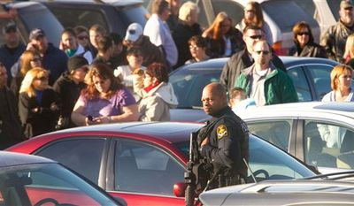 A Omaha police officer stands with a rifle as parents wait for students of Millard South high school to be released after a school shooting Wednesday  Jan. 5, 2011, in Omaha Neb. Police say 17-year-old Robert Butler Jr. opened fire Wednesday at Millard South High School, wounding the school's principal and vice principal. The vice principal died in hospital hours later. (AP photo/Chris Machian)