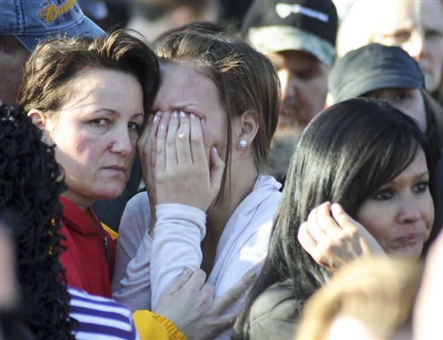 An unidentified student, center, is united with a loved one, in Omaha, Neb., Wednesday, Jan. 5, 2011, outside the Millard South High School after a student shot and wounded two adults, causing students to rush into a school kitchen to take cover before his body was found in a car about a mile away. (AP photo/Dave Weaver)