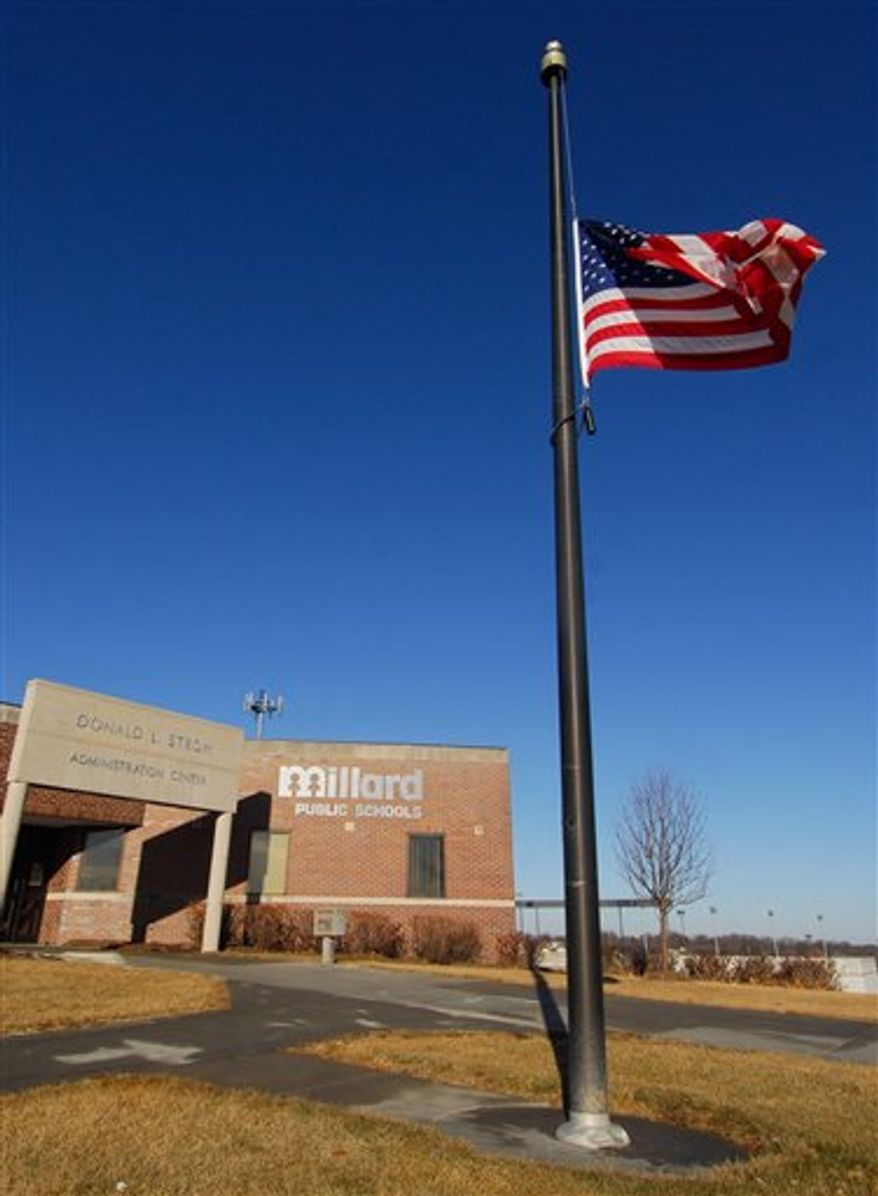 The U.S. flag flies at half staff Thursday Jan 6, 2011, outside of the Millard Public Schools Administration Center in Omaha, Neb. The 17-year-old gunman who opened fire at his Nebraska high school, killing an assistant principal, had been suspended from class and removed from the building hours earlier for driving on an athletic field, police said Thursday. (AP Photo/Dave Weaver)