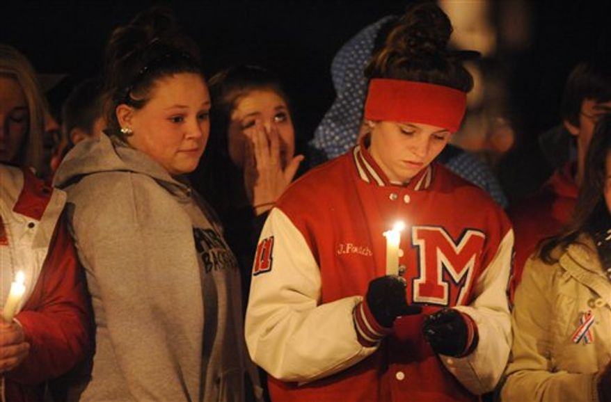 Millard South High School students hold a candle light vigil in front of the school Thursday Jan. 6, 2011, in Omaha, Neb. A student opened fire killing the assistant principal, and wounding the principal on Wednesday. (AP Photo/Dave Weaver)