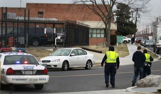 ** FILE ** Law enforcement officials are seen near a postal sorting facility in Washington on Friday, Jan. 7, 2011, after a package ignited. The package ignited at the facility, a day after fiery packages sent to Maryland's governor and transportation secretary burned the fingers of workers who opened them. (AP Photo/Alex Brandon)