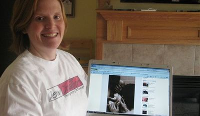 Birth photographer Laura Eckert poses in her living room in Shueyville, Iowa on Thursday, Jan. 6, 2011, with one of the photos she had taken of her friend's baby's first moments. Facebook apologized to Eckert on Thursday, saying the company mistakenly disabled her account in December after saying pictures she posted did not comply with its policies prohibiting nudity. (AP Photo/Ryan J. Foley)
