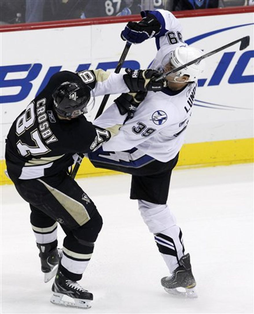 Pittsburgh Penguins' Sidney Crosby (87) collides with Tampa Bay Lightning's Mike Lundin (39) in the third period of an NHL hockey game in Pittsburgh on Wednesday, Jan. 5, 2011. The Penguins won 8-1. (AP Photo/Gene J. Puskar)