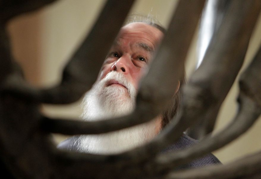 Bill Pickard is framed by the ribs of the Conway Mastodon at the Ohio Historical Society in Columbus, Ohio Thursday, Jan. 6, 2011. The skeleton of the Ice Age pachyderm is being disassembled so it can be reassembled in a more flattering position. (AP Photo/Mark Duncan)