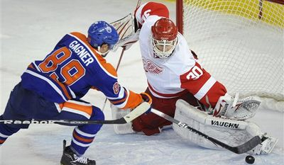 Edmonton Oilers' Gilbert Brule, right, scores on Detroit Red Wings goalie Chris Osgood as Detroit's Brian Rafalski looks on during the first period of an NHL hockey game in Edmonton, Alberta, on Tuesday, Jan. 4, 2011. (AP Photo/The Canadian Press, John Ulan)